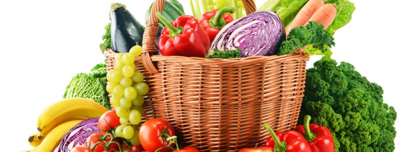 Wicker basket with assorted organic vegetables and fruits  isolated on white